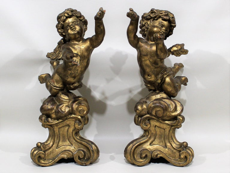Pair of gilt carved wood putti figures atop decorative tripod bases.