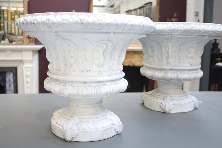 Antique pair of small mid-Victorian cast iron garden urns with fine decoration. Primed ready for painting.  Overall 15.5