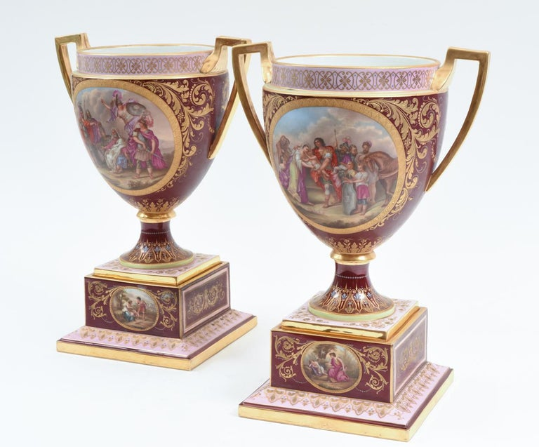 Antique hand painted pair of Royal Vienna Porcelain uncovered decorative piece / urn. Each piece have two gilt side handles with hand painted panels design details. Each one is set on squared hand painted design details holding base. Each piece /