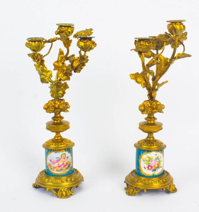 This is a delightful antique pair of 19th century French Sèvres porcelain mounted ormolu candelabra.   The cylinder-shaped Sèvres porcelain columns feature hand painted panels of summer flowers and cherubs on a bleu celeste ground with gilt