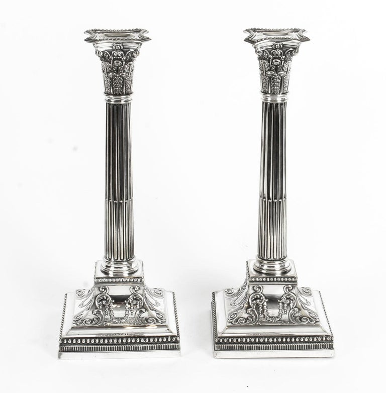 This is an exquisite pair of antique English silver plated candlesticks in neoclassical Corinthian column style and bearing the makers marks, inside the sconces, of the renowned silveresmith, James Dixon & Sons, Sheffield, circa 1870 in