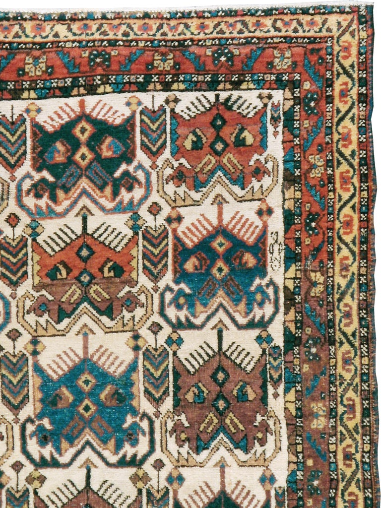 An antique Persian Afshar rug from the early 20th century. Vaguely insectoid unidirectional palmettes in mostly red and blue are displayed in seven rows on the ivory ground. This is a classic SE Persian Afshar design seen on saddlebags and scatter