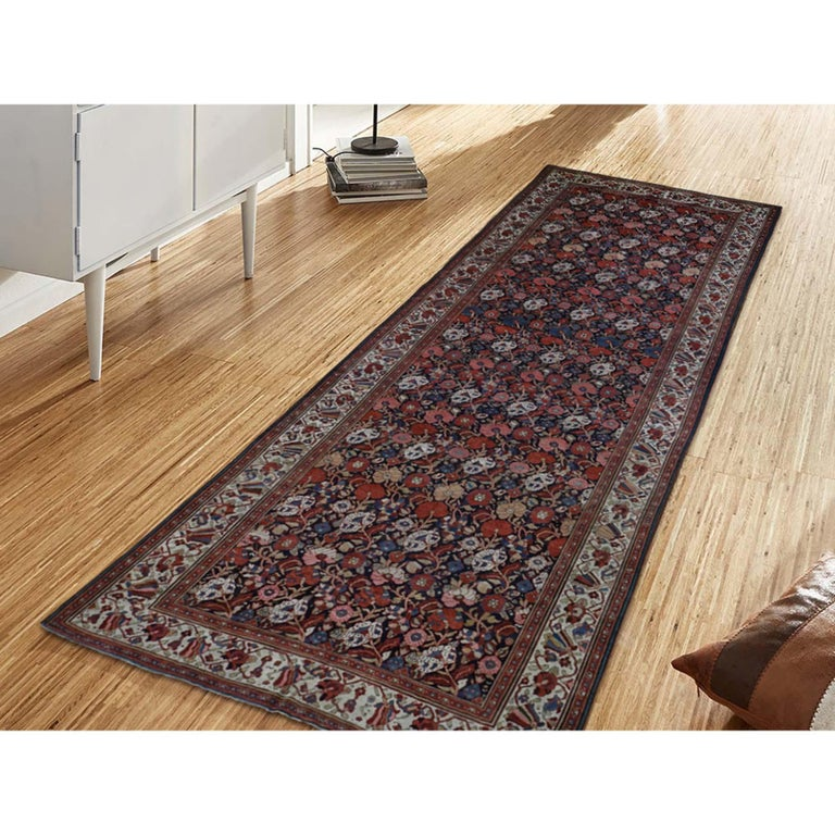 This is a truly genuine one-of-a-kind antique Persian Bakhtiari wide gallery runner flower design rug. It has been knotted for months and months in the centuries-old Persian weaving craftsmanship techniques by expert artisans.    Primary