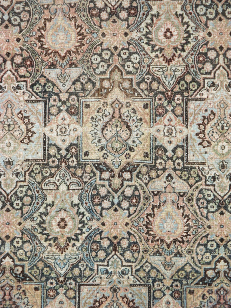 An antique Persian Dorokhsh carpet from the early 20th century. The dark brown field features squared cartouches enclosing palmettes alternating with palmettes-in-lozenges in offset rows. The ivory main border displays fan palmettes and other