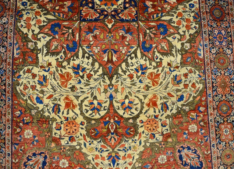 An antique Persian Farahan carpet dating to circa 1890 in rich hues of red, cream, and light blue in an intricate design. This carpet utilizes pure handspun wool and organic vegetable dyes, it measures 4'1