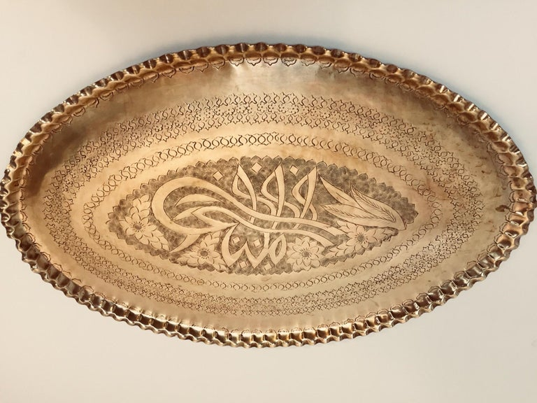 Antique oval hand-etched, hammered and embossed, chiseled Persian polished brass tray with pie crest edges. Very finely hammered in floral Moorish designs and Kufic Islamic calligraphy. Great Middle Eastern collector metal work platter decoration.