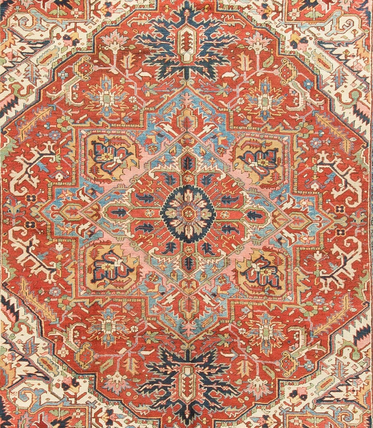 Antique Persian Heriz rug circa 1900. This wonderful antique Heriz rug has a light and easy flow to the design and color scheme. The combination of the soft blue in the centre surrounded by reds and them all enclosed in ivory creates the perfect