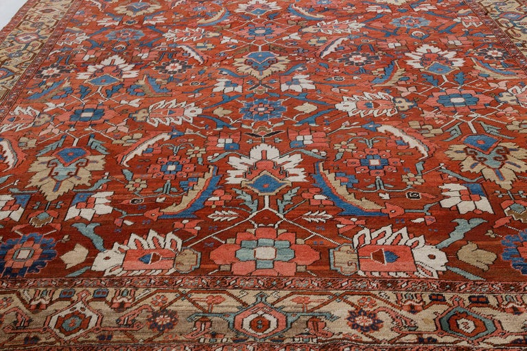 Antique Persian Heriz rug in blue, pink, red, white, and yellow Size: 11'0