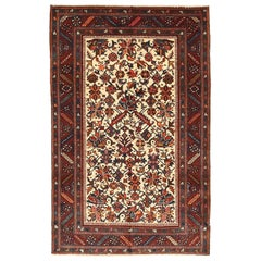Antique Persian Heriz Rug with Navy and Red Floral Motifs on Ivory Field