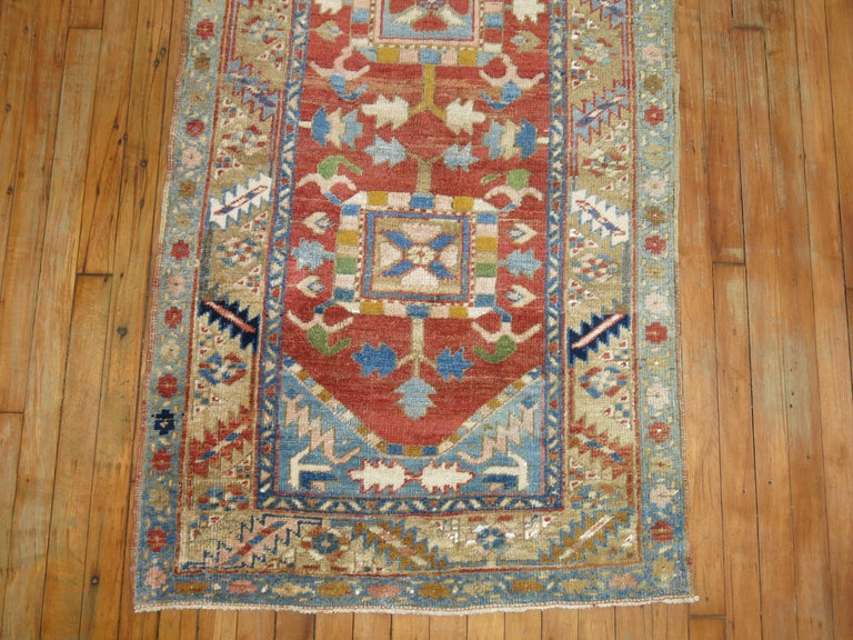 A one of a kind decorative antique Persian Heriz runner.  With distinctive large-scale motifs and a wide ranging palette of warm colors, the antique Heriz carpet is probably the most popular of the Persian village carpets. In constant, increasing