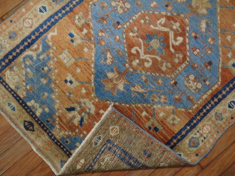Colorful antique Persian Heriz rug featuring accents in orange and sky blue.