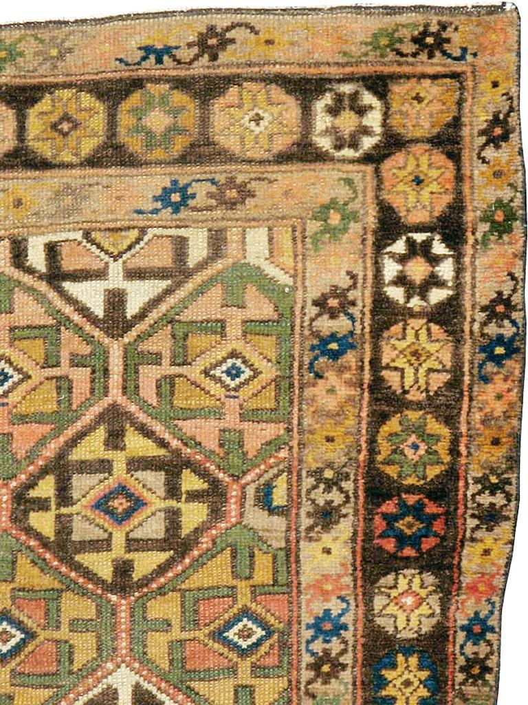 An antique Persian Kurdish carpet in runner format from the early 20th century. The western Persian Kurdish tribes often employed repeating geometric field designs, as here, with hexagonal lattices enclosing square and arrowhead cruciforms. There is