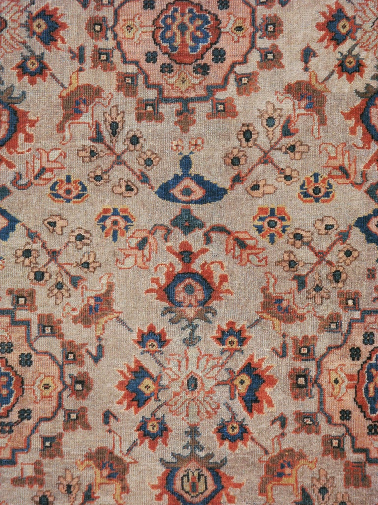 An antique Persian Mahal carpet from the early 20th century. The slate grey ground show three staggered columns of bud-edged quatrefoils with oblique thin flowering stems. This unconventional design is framed by a more standard red border of