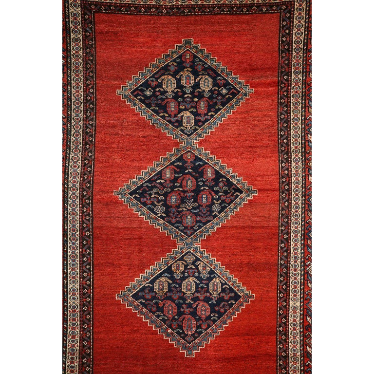 This antique Persian Malayer carpet in pure wool and vegetable dyes circa 1900 features a triple diamond central medallion with an intricate multiple band border and vibrant red field. Its organic coloration of vegetal dyed red and indigo creates a