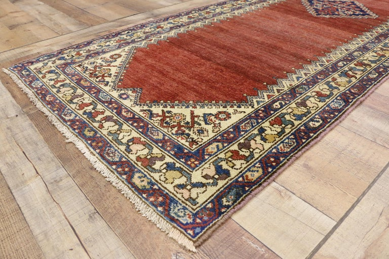 76543, antique Persian Malayer runner, hallway runner. This hand knotted wool antique Persian Malayer runner features a stepped lozenge center medallion floating on an abrashed red field. Rows of small pyramids with cruciform tops line the edges,