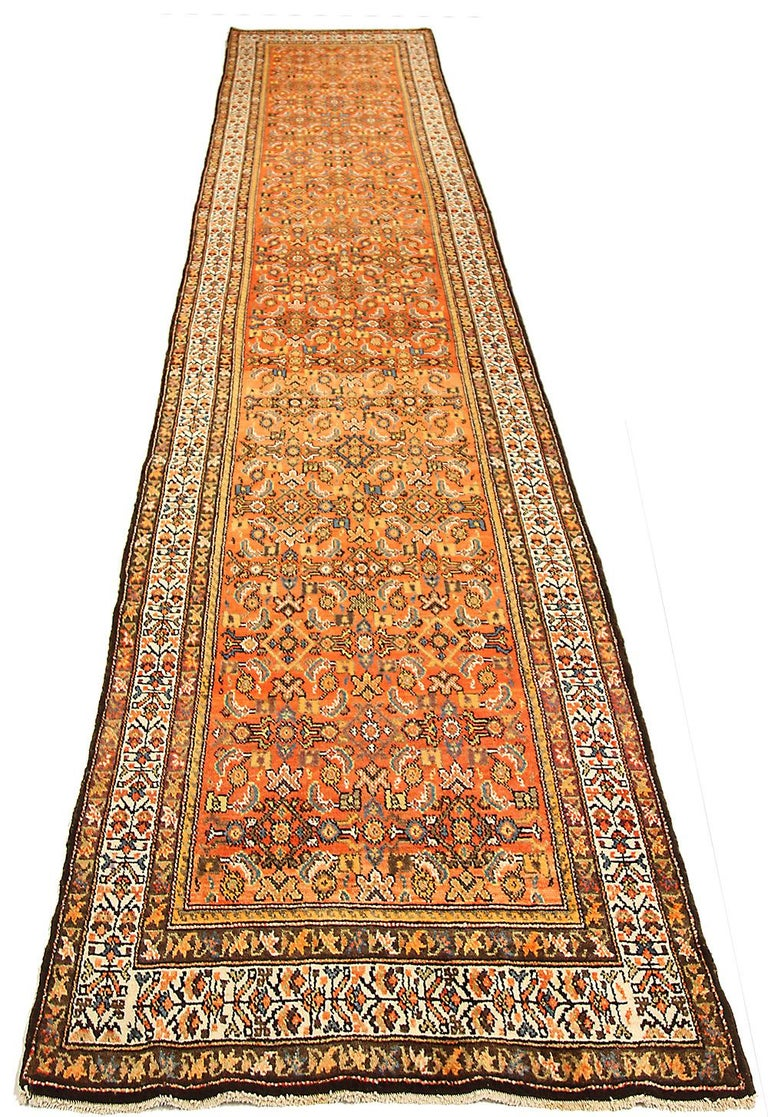 Antique Persian runner rug handwoven from the finest sheep's wool and colored with all-natural vegetable dyes that are safe for humans and pets. It's a traditional Malayer design featuring blue and white floral details on an orange and red field.
