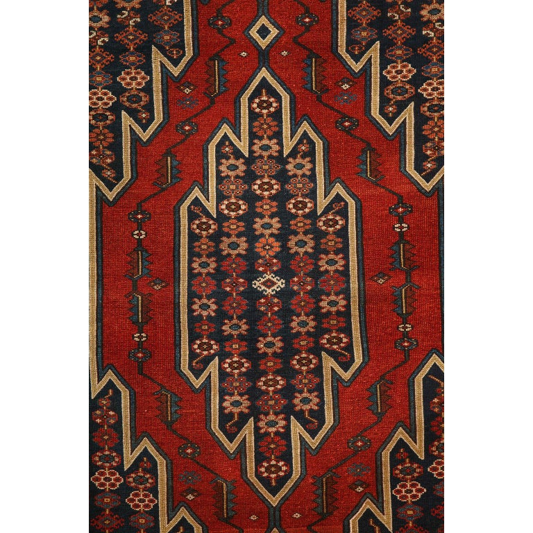 This antique Persian Mazlaghan carpet in pure wool and vegetable dyes circa 1920 features a geometrically striking central medallion with layered borders and a patterned field of stylized floral motifs. Its bold patterning is balanced by its organic