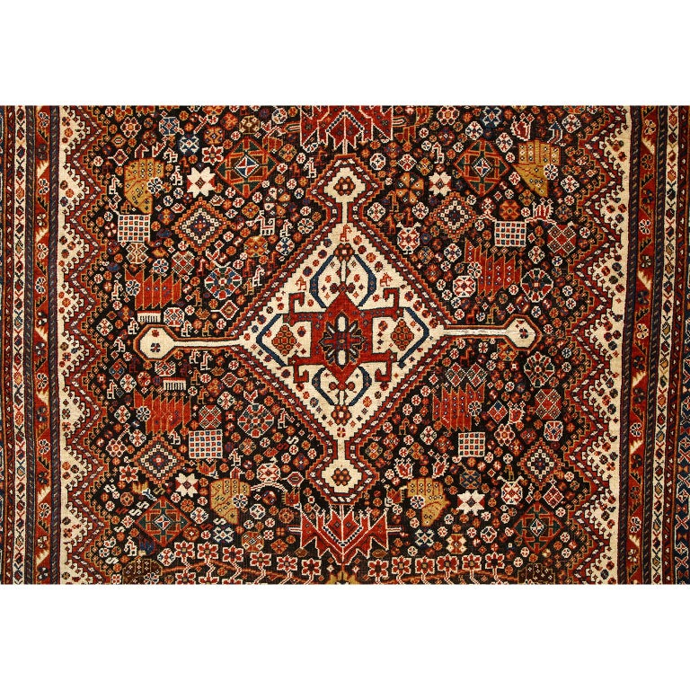 This antique Persian Qashqai Kashkooli carpet in pure handspun wool and vegetable dyes circa 1900 features a central stylized