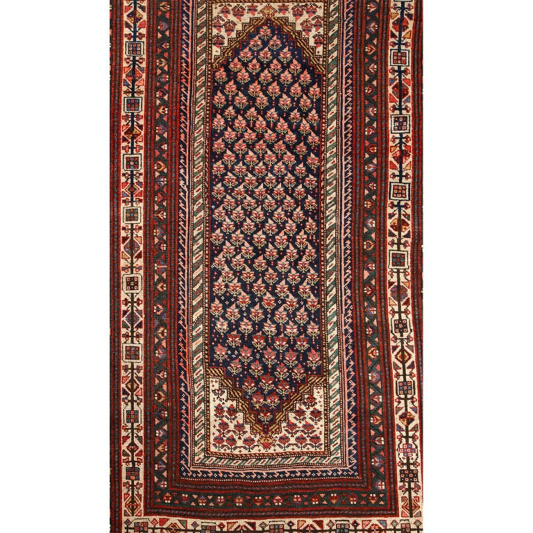 This antique Persian Senneh carpet in pure handspun wool and vegetable dyes circa 1900 features a floral patterned central medallion and field with multiple borders of alternating geometric designs. Bright cream colored wools and deep indigo