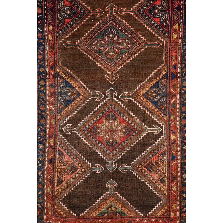 This antique Persian Seraband carpet in pure wool and vegetable dyes circa 1900 features a central mirrored band design with intricately detailed and layered borders. Hand knotted in pure handspun wool upon a woolen warp and weft, its organic design