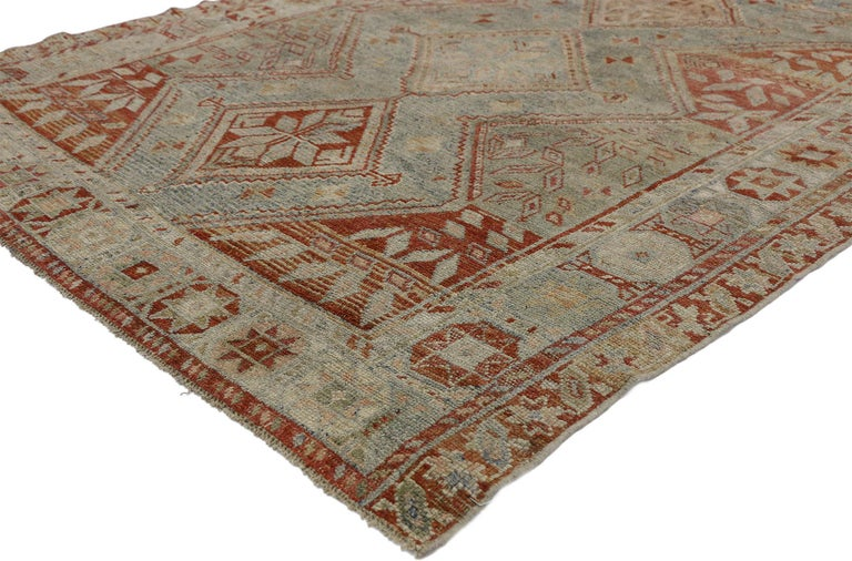 52455, antique Persian Shiraz rug with Subtle Bungalow style. This hand knotted wool antique Persian Shiraz rug features a subtly bungalow style with a diamond pattern in gradated, muted blues and bright red hues. A stacked pole medallion of