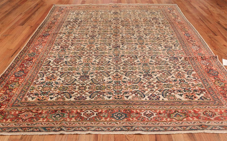 Antique Sultanabad carpet, Oorigin: Persia, circa 1920. The delightful display of colors and floral shapes in this Sultanabad rug create an almost living, breathing universe for the viewer to explore. Several rich borders stand against each other,