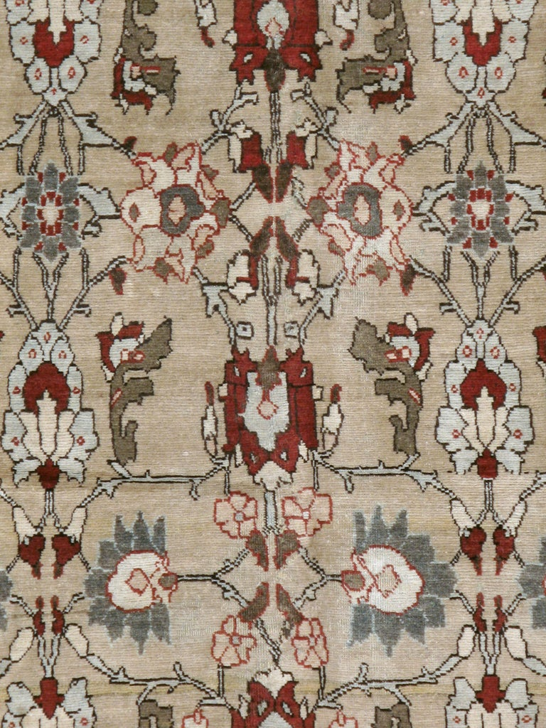 An antique Persian Tabriz carpet from the early 20th century. A spacious and nearly rustic version of the popular Herati allover pattern ornaments the oatmeal field of this Tabriz rug. The weavers may have been inspired by Malayer or other village