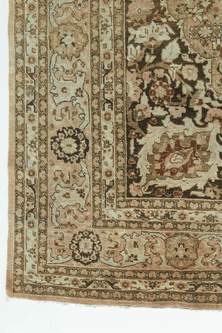 This antique Tabriz in the style of the legendary designer of courtly rugs, Haji Jalili, features a soft brown field with darker brown lobbed medallion and spandrels, and accents of rose, ivory, taupe and burgundy. The densely filled design features