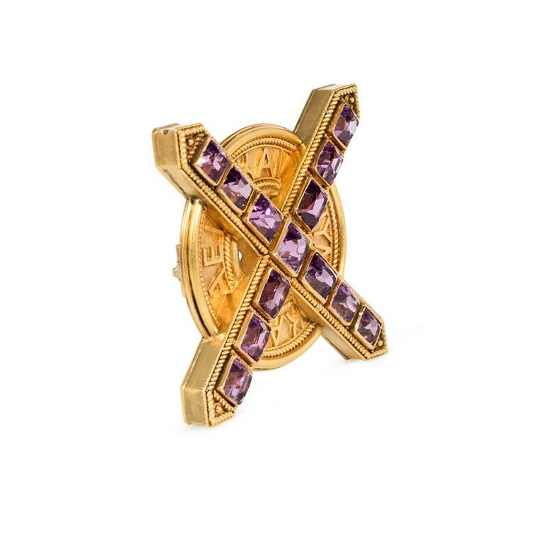 An antique gold brooch in the Etruscan Revival style comprised of a rectangular-cut amethyst