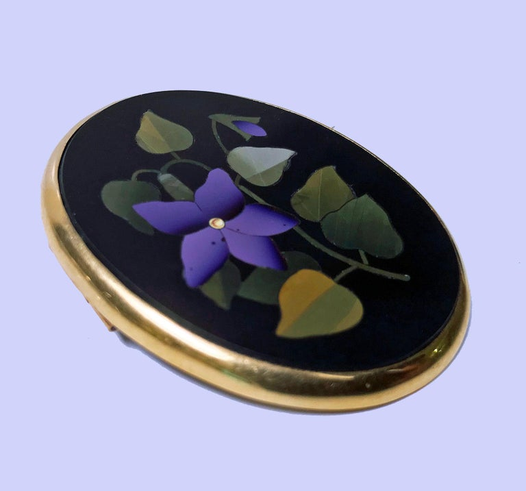 Antique 18K Gold Pietra Dura Brooch, Italy C.1875. Oval shape, fine pietra dura floral  green, lilac inlay colors, 18K surround gold mount. Gold acid tests 18K. Measures: 1.75 x 1.50 inches. Total Item Weight: 13.36 grams.