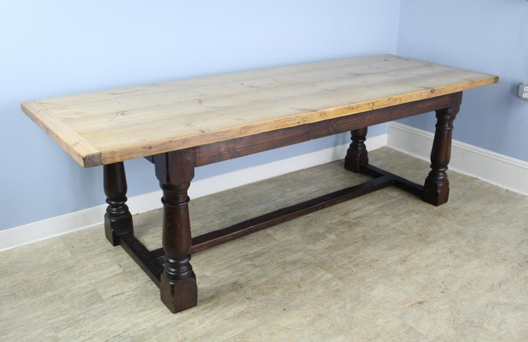 A dramatic dining table with a bleached thick pine top and a painted black refectory base. Large eye catching turned legs under a chunky butcher block top. Glamorous! With 63.25 inches between the legs, this table can accommodate 8. Measures: 24.25