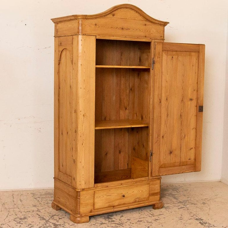 It is the beauty of the warm, aged wood that captures your attention in this pine armoire that stands almost 6 1/2ft tall. The lovely curves of the panels and bonnet add a touch of grace while the large dovetail joints and hardware remind us of its