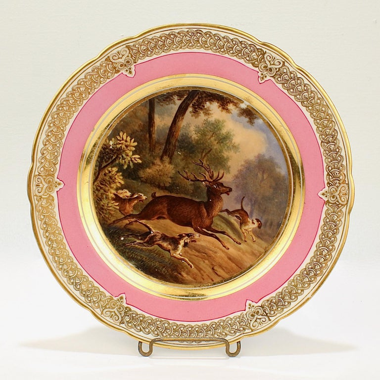 A wonderful antique 19th century Paris porcelain plate.  With a hand painted scene of a hunt scene in a bucolic landscape including a large buck (10 point) and 3 hounds in chase.   It has a rich pink border and an elaborate gilt design to the