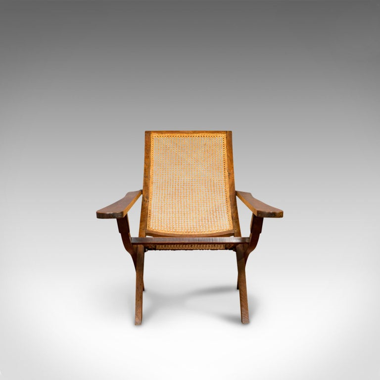 This is an antique plantation chair. An English, solid teak and bergere cane steamer-deck armchair, or garden lounger, dating to the Edwardian period of the early 20th century, circa 1910.