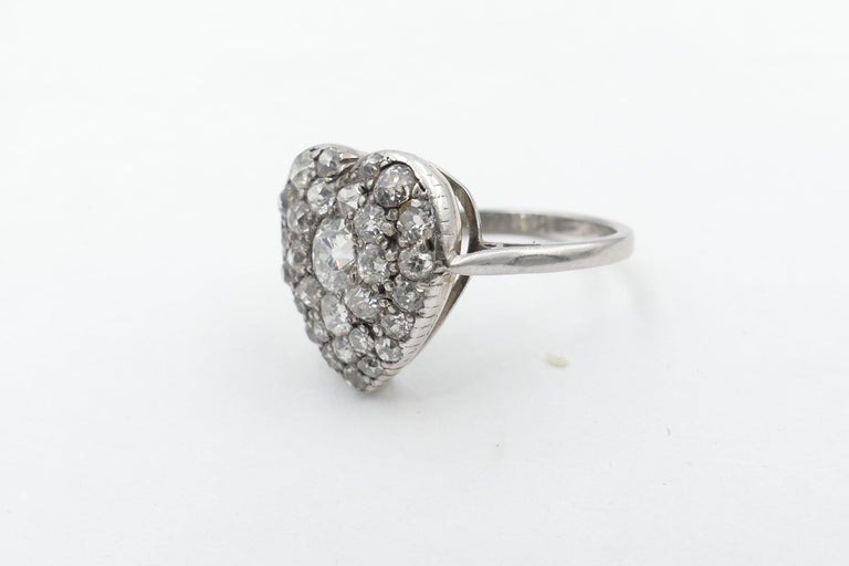 The Centrepiece of this beautiful Antique Heart Shaped Diamond Ring is one Old EuropeanCut Diamond 4.10 X 4.28 X 2.86mm, Colour G, Clarity SI1. It is surrounded by 6 Old European Single Cut Diamonds, Colour G/I & Clarity SI1-I1 & Bead Set. The Band
