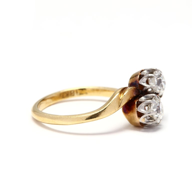 An antique platinum topped 18 karat yellow gold diamond ring. A bypass, toi et moi design with two prong set old European cut diamonds weighing approximately .88 total carats and a slightly tapered shank.  Stones: - diamonds, 2 stones - old European