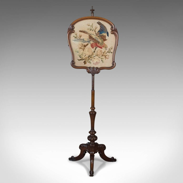 This is an antique pole screen, an English, early Victorian fire screen with needlepoint tapestry panel dating to circa 1850.  Raised on a turned mahogany Stand with good color and grain interest A tripod of cabriole legs featuring carved 'C'