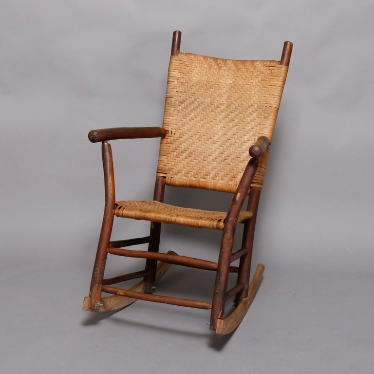 An antique and Primitive style Old Hickory School 3-piece porch set offers stick form armchair, rocker and settee having caned seats and backs, circa 1910  ***DELIVERY NOTICE – Due to COVID-19 we are employing NO-CONTACT PRACTICES in the transfer of