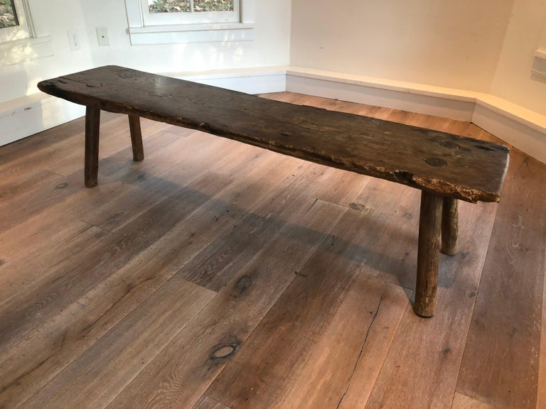 An antique primitive wood long bench. Great dowel construction and patina to wood. Chipping and wear along edges consistent with age and use.