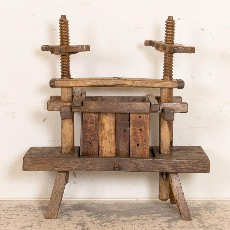 There is heft and substance to every part of this hand-built wine press, making it a fun and unusual find. Visually impressive are the hand-turned screws with carved handles and the old, wrought iron bolts and straps that support it. Every crack,