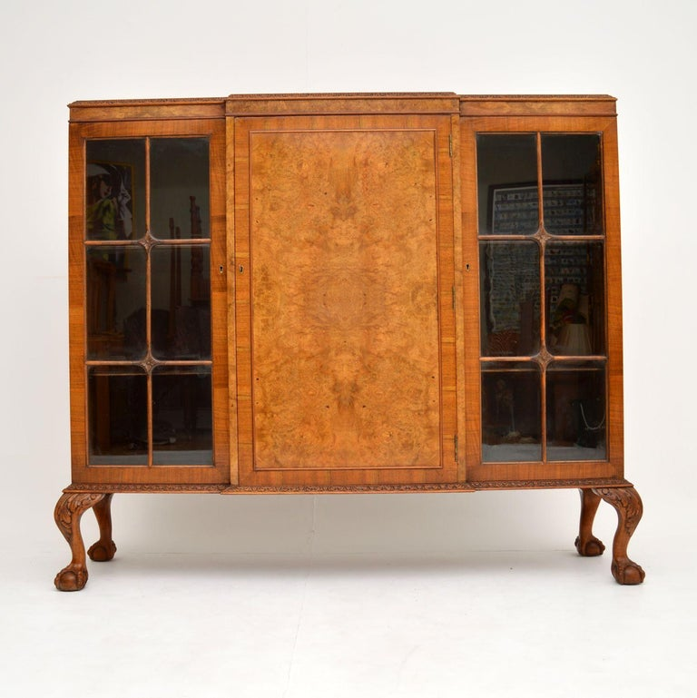 An excellent and fine quality antique bookcase, beautifully made from walnut. It is in the antique Queen Anne style, and dates from circa 1920s-1930s.  This is a nice size and offers lots of storage space in the three cabinet compartments, the