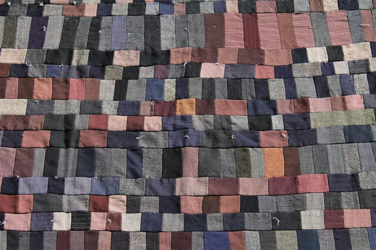 This early 1900s all wool crazy quilt / postage stamp wool suiting quilt has a cotton flannel backing. The condition is very good.