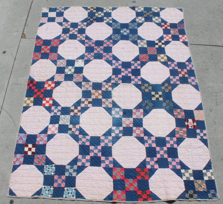 This early red, white and blue calico and indigo blue fabrics has a homespun backing. The binding edges have been repaired in some areas a long time ago. The quilts is in good condition otherwise.