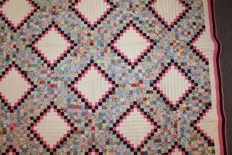 This fine tiny postage stamp Irish chain quilt is in pristine unwashed , never used condition. This amazing beauty has a black and pink trim and triple borders. This fine quilt was found in Ohio and has a pink polished cotton backing. The piece wok