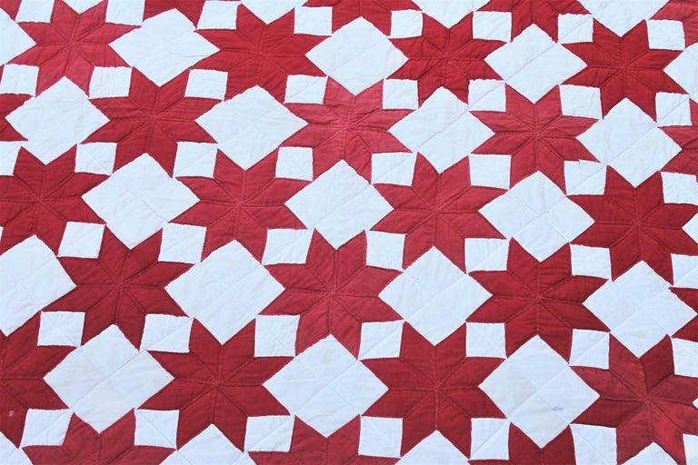 This fun and graphic red and white stars quilt with inner saw tooth border is in good condition. The binding is original to the quilt and the backing is in red fabric. The condition is good.
