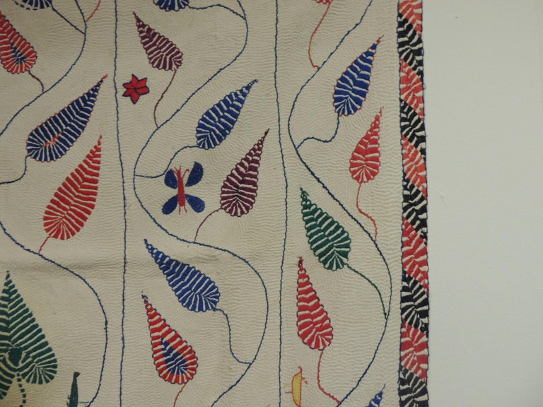Antique quilted Indian Paisley wedding ceremonial colorful blanket with embroidery border. Solid natural background and embroidery in shades of red, blue, green, yellow, orange, purple, royal blue and red. Depicting embroidered birds, butterflies,