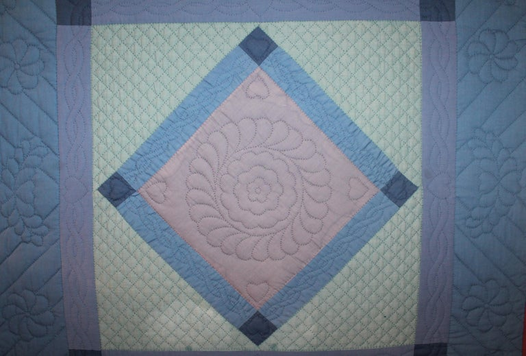 Amish mounted diamond in a square crib quilt from Lancaster County, Pennsylvania. This rare and very unusual all cotton crib quilt is in very good condition with slight lighted colors.