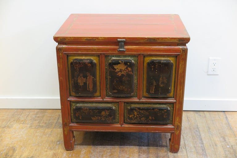 Chinese Qing Dynasty chest with drawers. Accentuated raised panels with scalloped edges make up all the front and side panels. Adorned with red lacquer decorated with regional images gold painted. The front panels have decorated borders highlighted