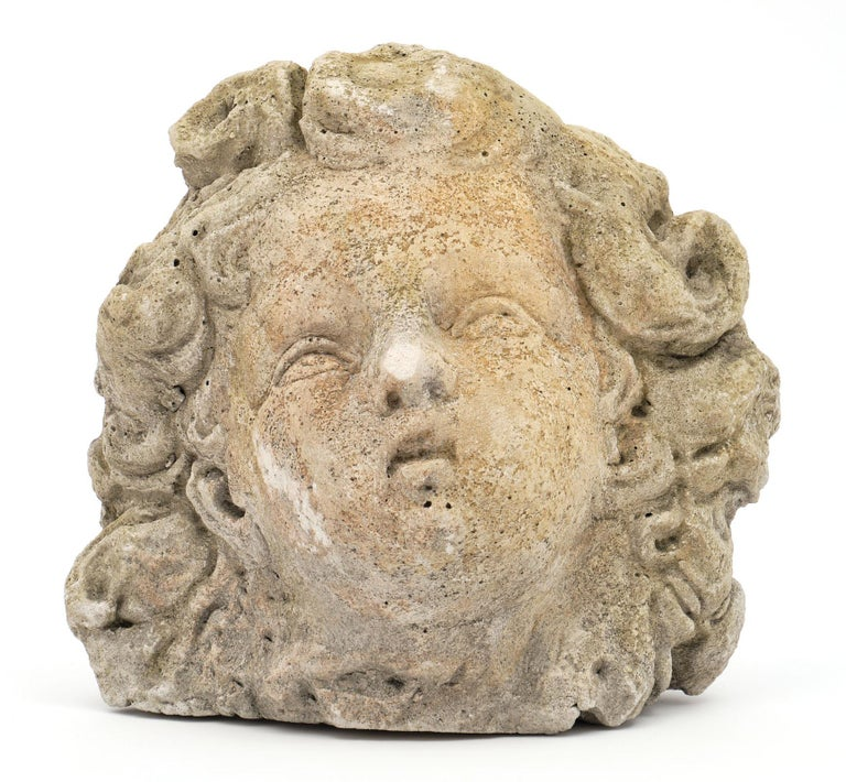 Antique reconstituted stone sculpture from a French garden. This stone ornament represents an angels head. We love the detail and patina of this unique piece.