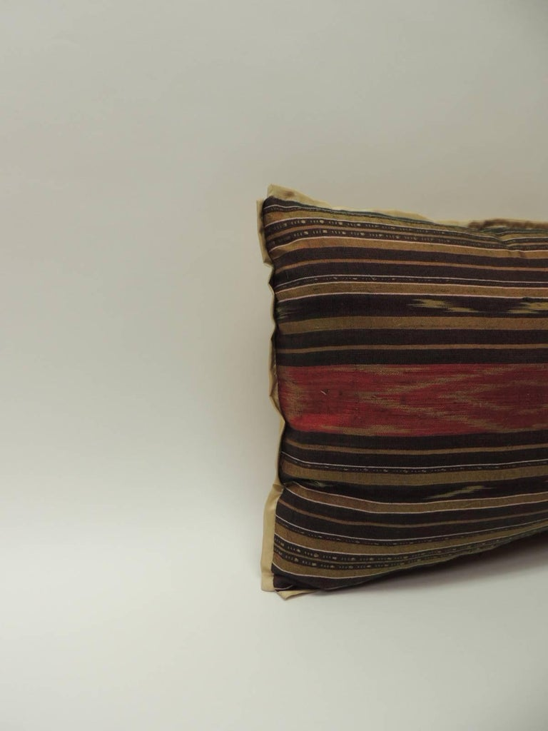 Vintage silk Laos bolster pillow. Traditional tribal pattern in shades of red, gold, brown, yellow and purple. Embellished with the ATG custom gold flat silk trim same as backing. Decorative pillow handcrafted and designed in the USA.  Closure by